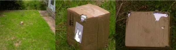 A parcel in a garden. The parcel has been damaged by a fox.