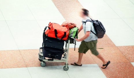Man pushing airport trolley