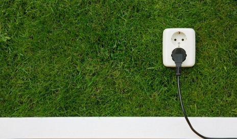 Plug socket on wall of grass
