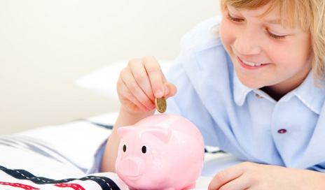 Boy saving money into piggy bank