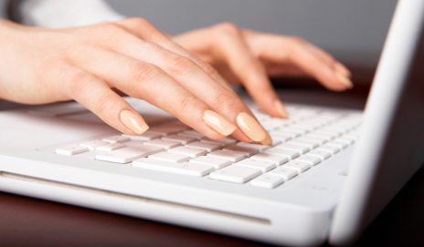 Woman's hands typing on white laptop