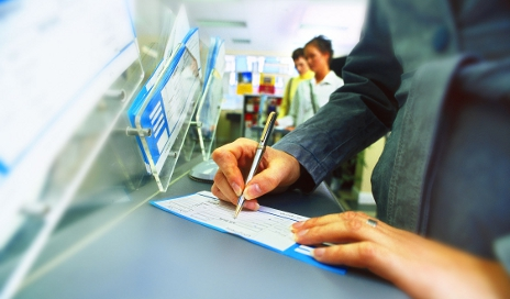 Woman using cheque book in bank