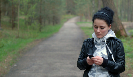 Woman texting in a forest