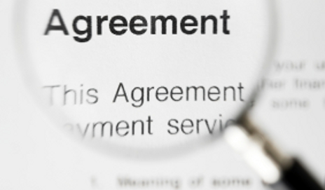 Magnifying glass over agreement paperwork