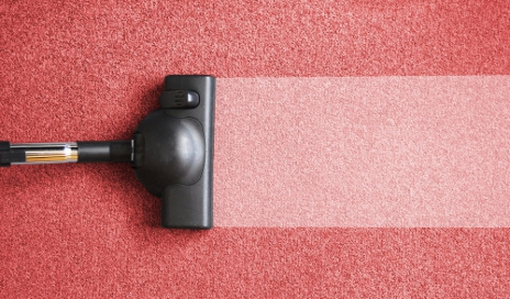 Vacuum cleaner on pink carpet