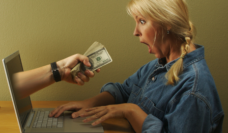 Woman surprised by money coming out of laptop