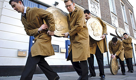 Workmen walking with giant pound coins