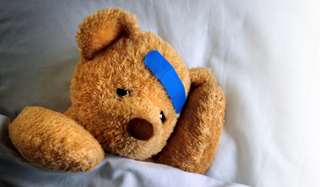 Sick teddy bear in bed