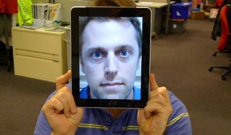 Ben Stevens holding a picture of himself on the iPad