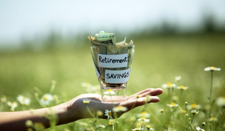 Hand holding jar of money in green field