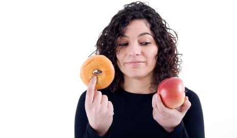 Woman weighing up donut next to apple