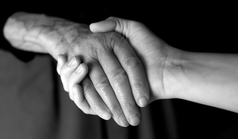 Elderly person's hand being held