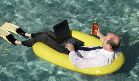 Business man using laptop in lilo