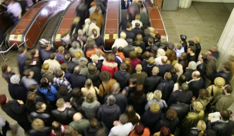 Crowd at top of station escalator