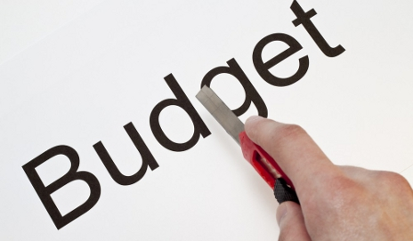 Hand cutting the word budget with a knife