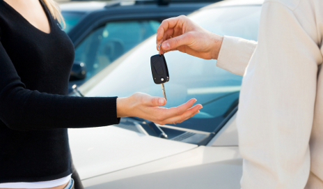 Man handing car keys to woman