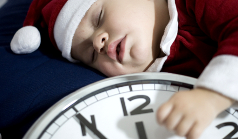 Baby in santa outfit next to clock