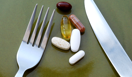 Pills on table with knife and fork