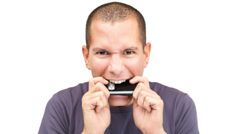 Man biting mobile phone angrily