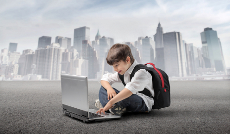 Boy on laptop in front of cityscape