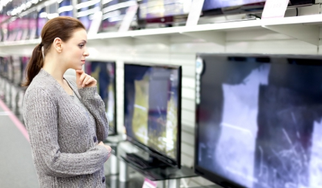 Woman looking at TVs in shop