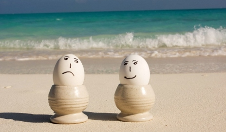 Two eggs on beach with happy/sad faces