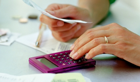Woman holding receipts and using calculator