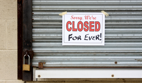 Closed sign on boarded up shop