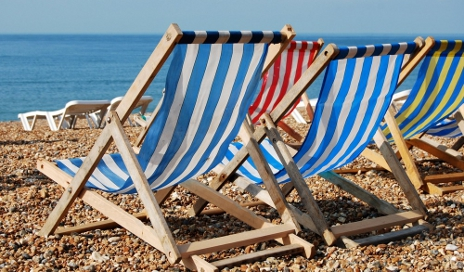 Deckchairs on pebbly beach