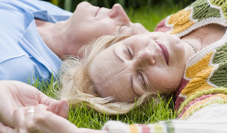 Elderly couple relaxing on grass
