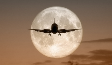 Plane flying in front of moon