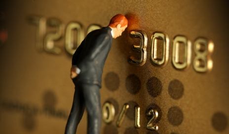 Figure leaning on credit card
