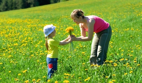 Girl giving mum flowers