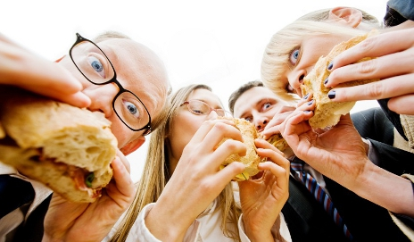 Group of people biting into sandwiches