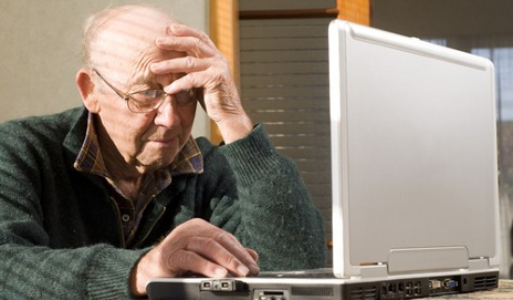 Elderly man looking confused at computer