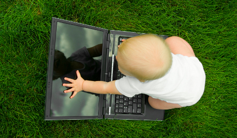 Baby looking at reflection in laptop