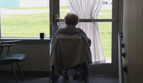 Elderly person looking out of window