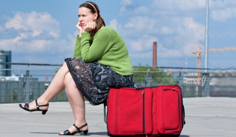 Woman depressed sitting on luggage