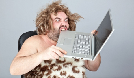 Prehistoric man eating laptop