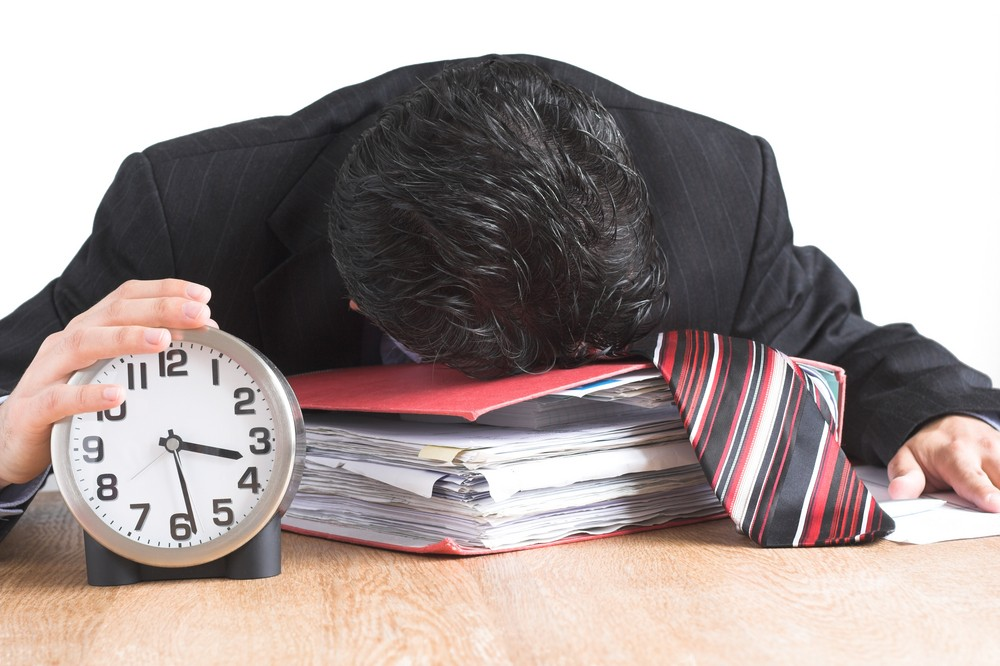 Business man asleep by clock