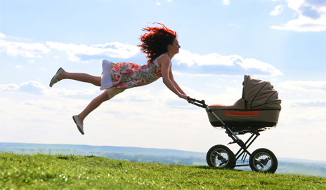 Mum leaping in the air with buggy