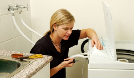 Woman fixing a washing machine