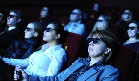 People wearing 3D glasses looking bored at cinema