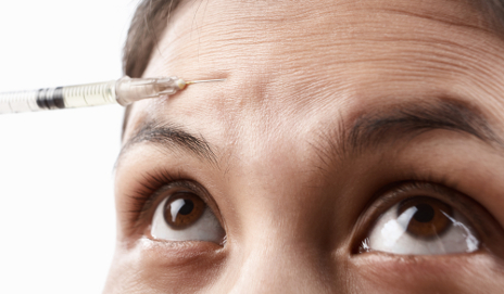 Scared woman having botox injection in forehead