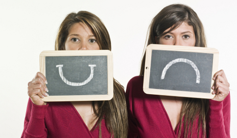 Two women holding up happy and sad faces