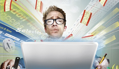 Man at computer with train tickets flying around him