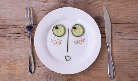 Sad face made out of vegetables on plate