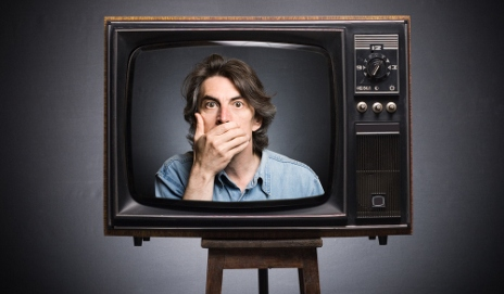 Man with hand over mouth on TV