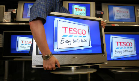 Man carrying TV with Tesco logo