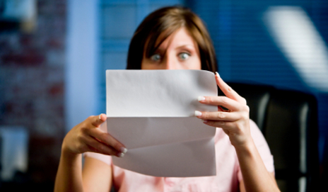 Woman reading bill looking shocked